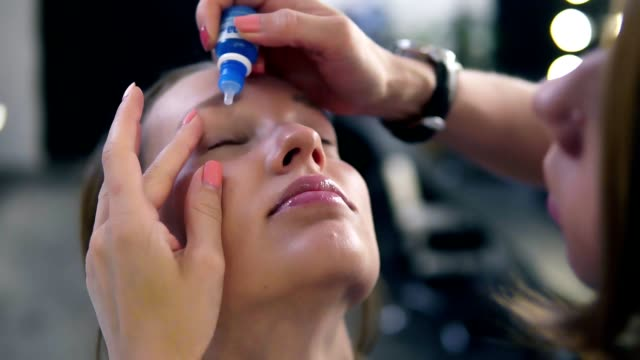 Woman with eye drops. Closeup of beautiful girl, make up master applying eyedrops in her eyes. Young female model with natural makeup video