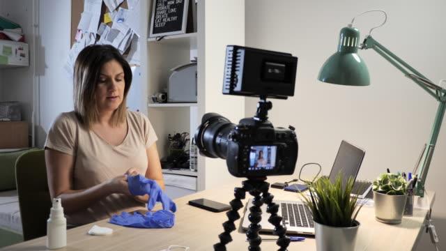 코로나바이러스 예방에 대해 이야기하는 얼굴 마스크와 장갑을 낀 여성 - influencer 스톡 비디오 및 b-롤 화면
