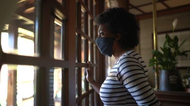 donna con maschera facciale che guarda attraverso la finestra e pensa a casa - inquadratura fissa video stock e b–roll