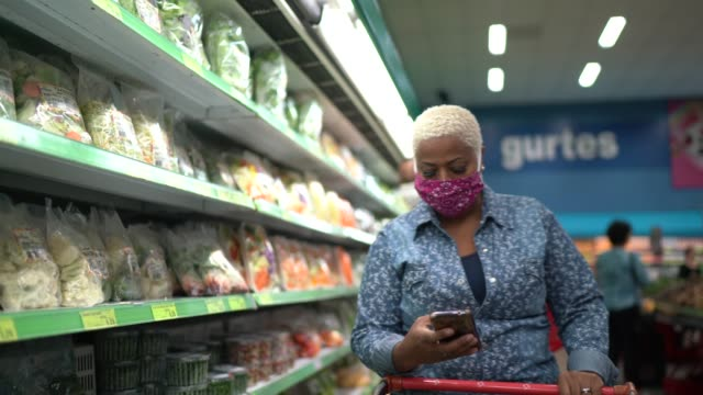 Woman with face mask walking and using mobile at supermarket