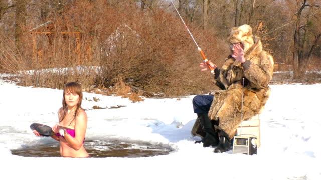 水の中で冬に手に魚を持つ女性。 - 漁師 外人点の映像素材/bロール