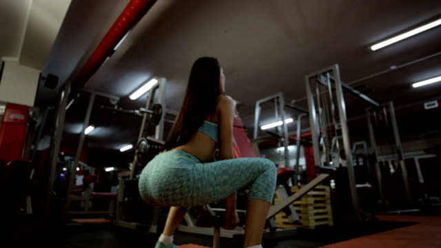 Woman with fit body doing squats in the gym video