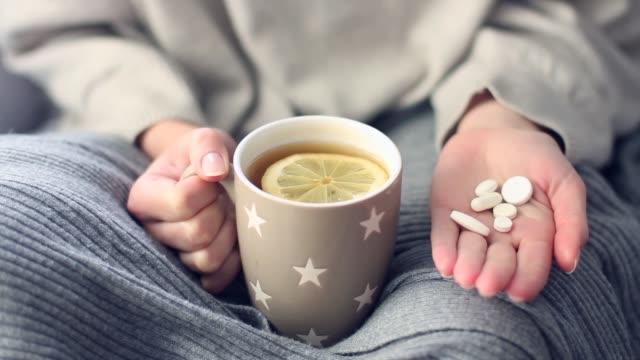 vidéos et rushes de femme avec la grippe prenant la médecine - boisson chaude