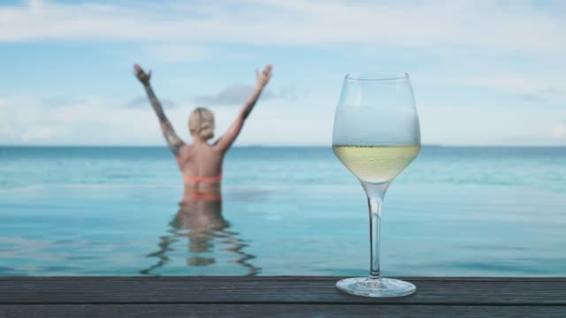 woman with glass of wine by the pool - cinemagraph - viziarsi video stock e b–roll