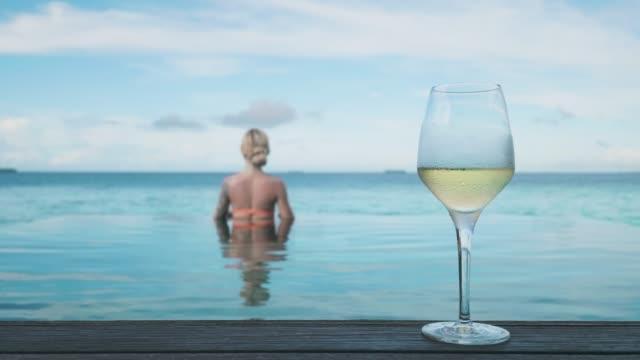 kvinna med glas vin vid poolen - cinemagraph - vitt vin glas bildbanksvideor och videomaterial från bakom kulisserna