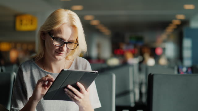 A woman with glasses and summer clothes is waiting for her flight at the terminal of the airport. Enjoys internet at the airport video
