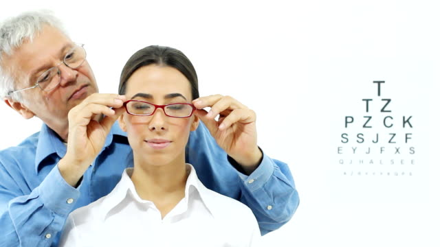 Woman with glasses Mature optometrist  putting  a glasses on the  face of beautiful young patient. eye chart stock videos & royalty-free footage