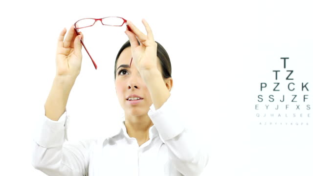 Woman with  glasses Beautiful young woman traying the  glasses on a  her face. eye chart stock videos & royalty-free footage