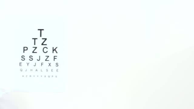 Woman with  glasses Beautiful young woman with glasses looking at the eye chart then she turning and looking at camera. Panning left. eye chart stock videos & royalty-free footage