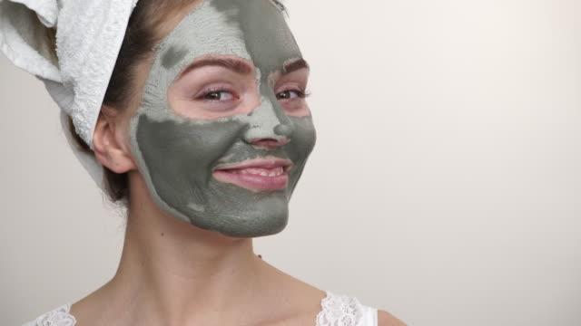 frau mit grünem ton-schlamm-maske auf gesicht 4k - kosmetische behandlung stock-videos und b-roll-filmmaterial