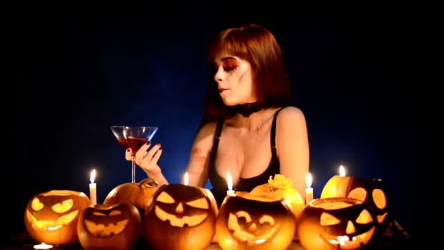 Woman with Halloween pumpkins holding cocktail glass video