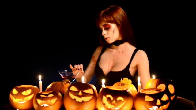 stockvideo's en b-roll-footage met vrouw met halloween pompoenen - martiniglas