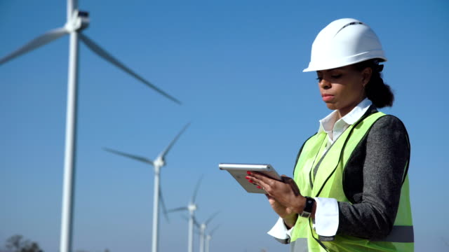 Woman with hard hat against wind turbine