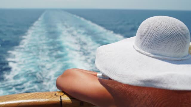 donna con cappello di godersi una vista sulla nave da crociera - crociera video stock e b–roll