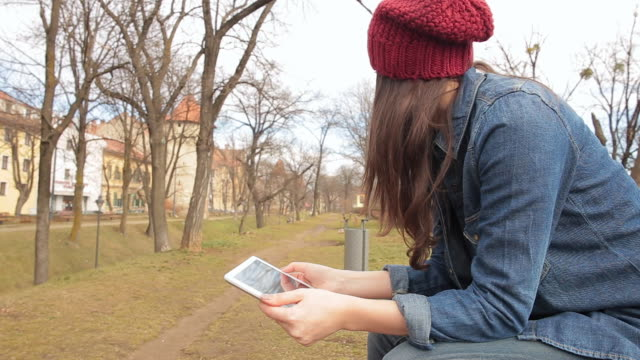 Woman with hat in the park using a digital tablet.