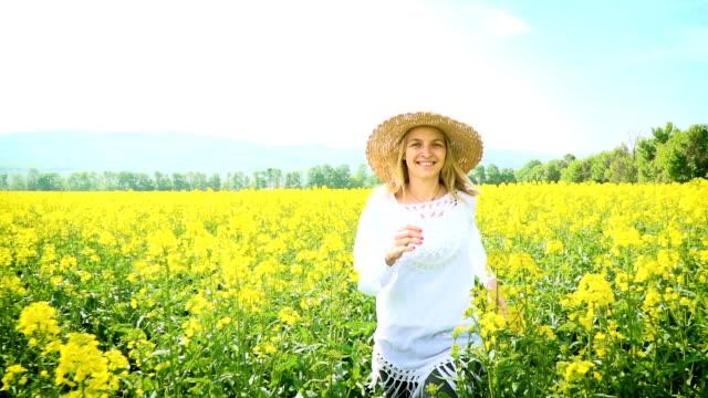 黄色開花菜の花畑で、帽子の女性 ビデオ