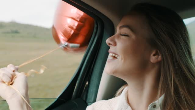 vídeos de stock, filmes e b-roll de mulher com chapéu na cabeça dela se divertindo no banco de trás do carro com balão de ar - veículo terrestre