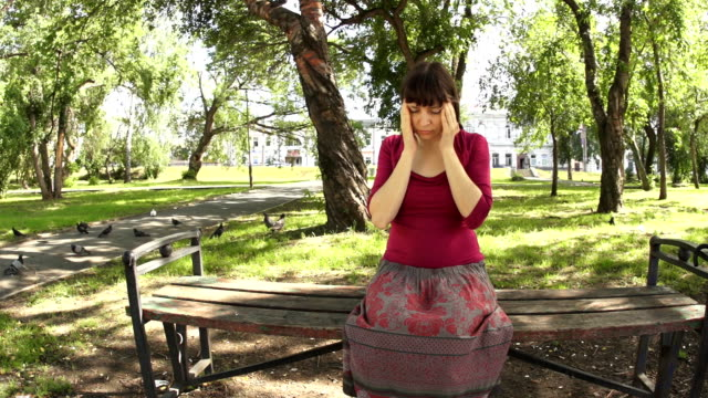 Woman with headache stroking whiskey with her eyes closed sitting in the park video