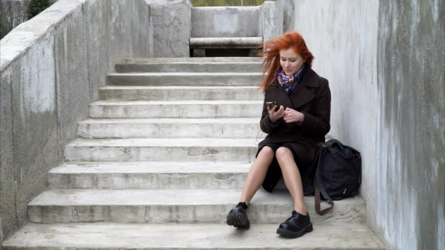 Woman with headphones and smartphone Young redhead woman is sitting on the stairs, listening to music, flipping the cell phone and slightly dancing stamping feet stock videos & royalty-free footage