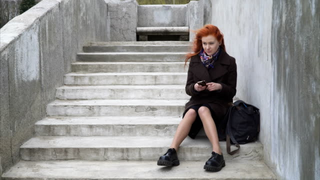 Woman with headphones and smartphone Young ginger woman is listening to music while sitting on the stairs outdoors stamping feet stock videos & royalty-free footage