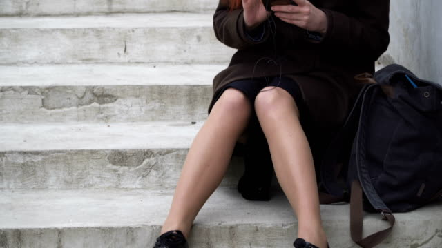 Woman with headphones and smartphone Cheerful woman is sitting on the stairs and listening to music, tapping the rhythm and flipping her smartphone, pan stamping feet stock videos & royalty-free footage