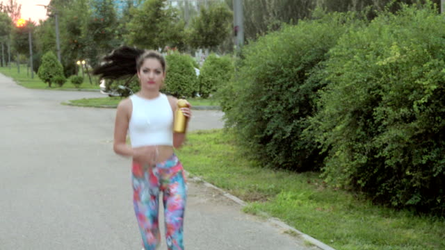 woman with headphones drinking water video