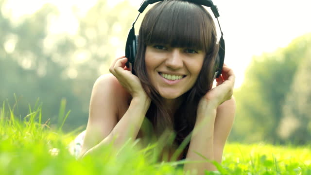 Woman with headphones listen to the music in park video