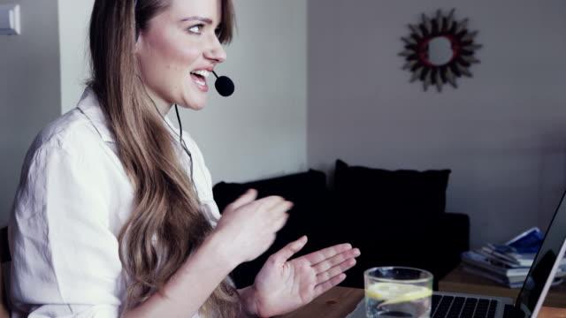 frau mit kopfhörer spricht über skype mit freunden. - wohngebäude innenansicht stock-videos und b-roll-filmmaterial