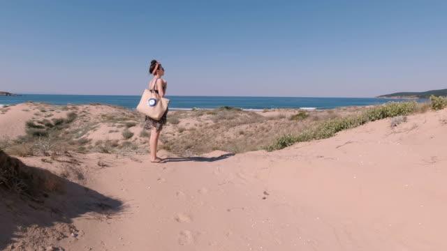 frau mit kopftuch stirnband, sonnenbrille und strandtasche zu fuß auf sanddünen. meereshorizont im hintergrund - menschlicher rücken stock-videos und b-roll-filmmaterial