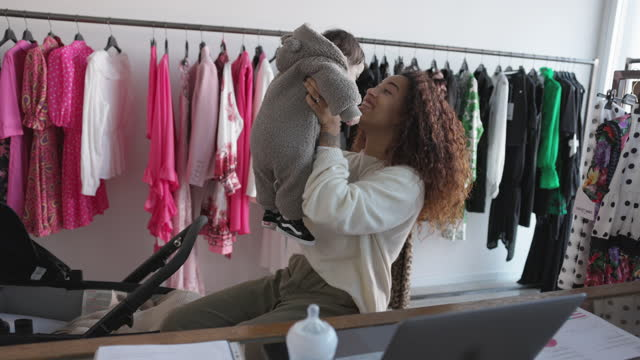 Woman with her baby girl working in her small business clothing store video