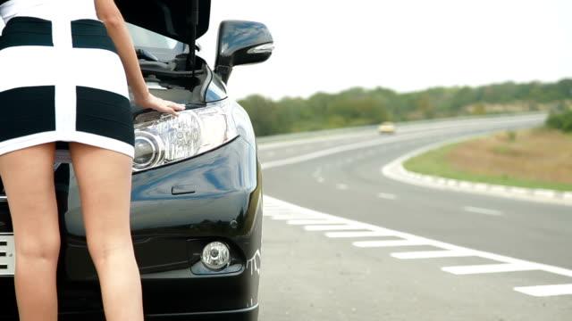 vídeos de stock e filmes b-roll de mulher com seu carro quebrado - berma da estrada