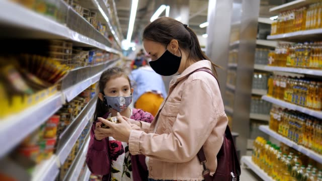 eine frau mit ihrer tochter in schützenden medizinischen masken im supermarkt während einer pandemie coronavirus. - krankheitsverhinderung stock-videos und b-roll-filmmaterial
