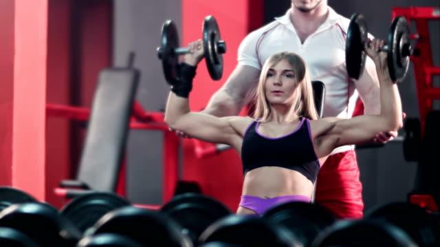 stockvideo's en b-roll-footage met vrouw met haar personal trainer in de sportschool trainen met halters - bankdruktoestel