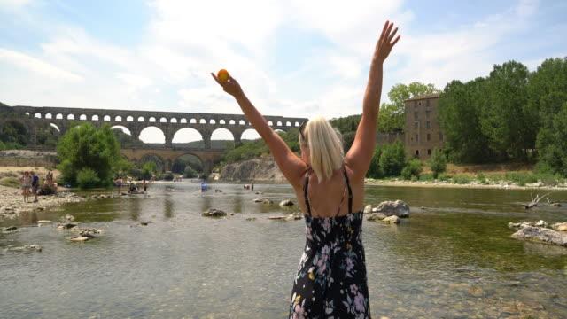 stockvideo's en b-roll-footage met ws vrouw met ijs wordt spannend door de pont du gard - pont du gard