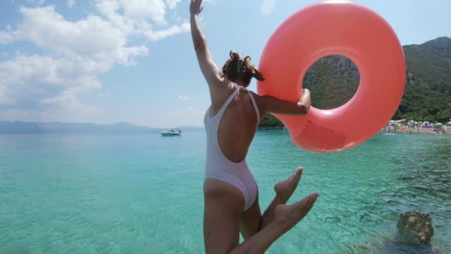 stockvideo's en b-roll-footage met ms-woman met opblaasbare ring springen in zonnige oceaan, peljesac, kroatië - opblaasband