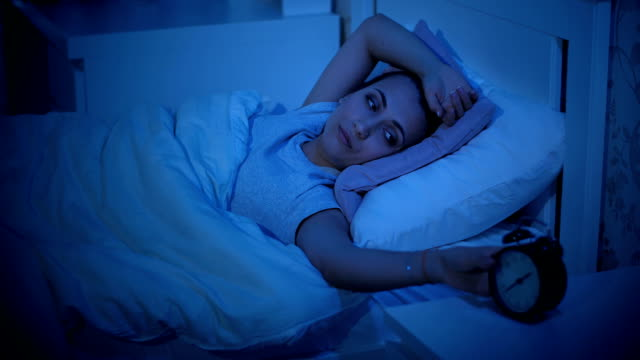 Woman with insomnia looks at the alarm clock Woman lies in bed and cannot fall asleep insomnia stock videos & royalty-free footage