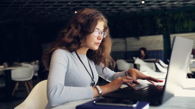 カフェでノート パソコン型テキストを持つ女性 ビデオ