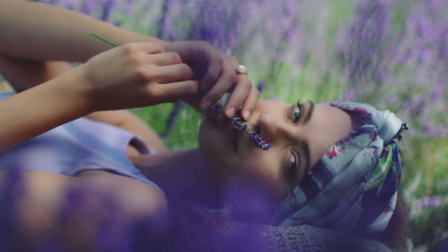 Woman with lavender flowers relaxing on field Smiling young woman smelling lavender flowers. Portrait of female is relaxing on field during vacation. She is wearing bandana. lavender plant stock videos & royalty-free footage