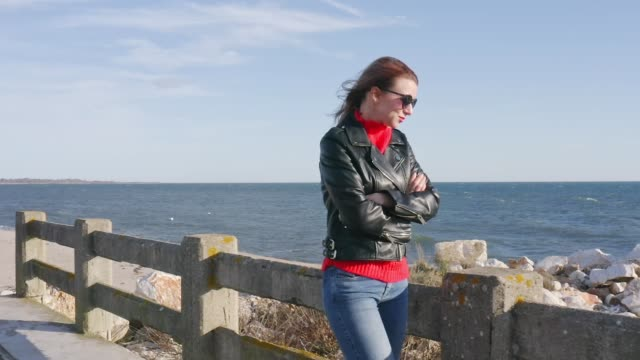Woman with leather jacket walking outdoors by the sea at day