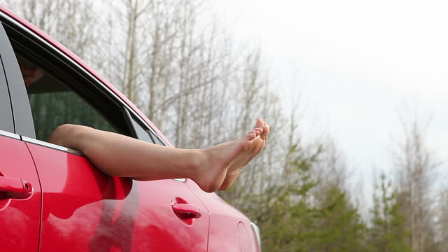Woman with legs out off car window (HD) video
