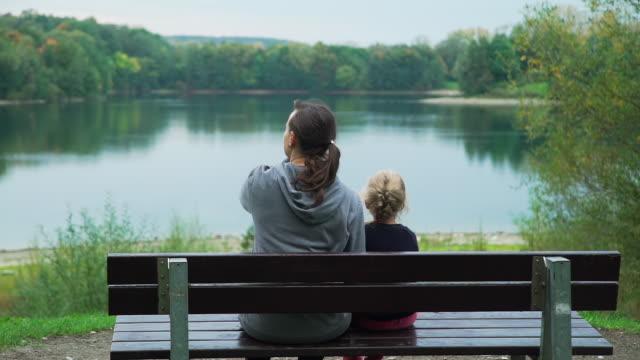 woman with little daughter enjoying view of lake - bench stock videos & royalty-free footage