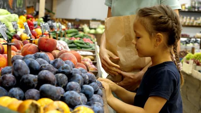 la donna con la figlia piccola sta scegliendo un frutto al negozio di alimentari - pesche bambino video stock e b–roll
