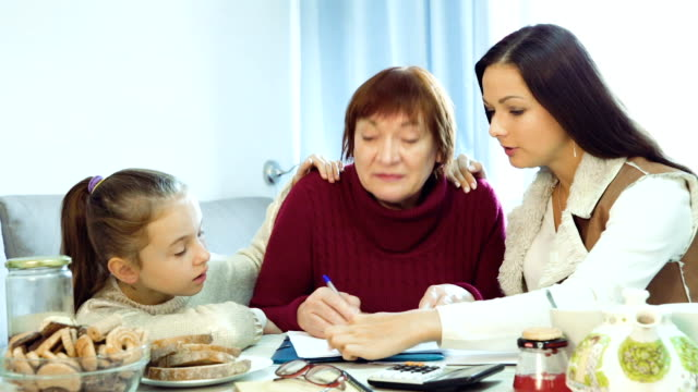 woman with little girl helping elderly mother with paperwork video