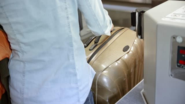 Woman with long blonde hair placing her baggage onto the conveyor belt at the check in desk at the airport video