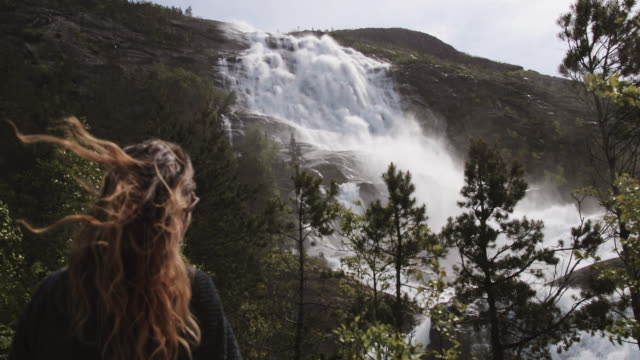 Woman with long hair by a huge waterfall in Norway