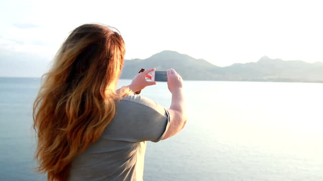woman with long hair makes a photo on the phone video