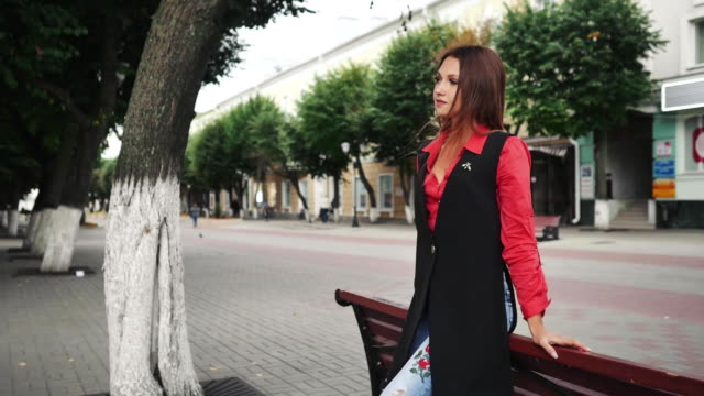 Woman with long hair rests on a bench outdoors at autumn day video