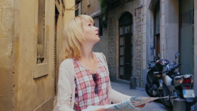 Woman with map walking along the narrow medieval city convict video
