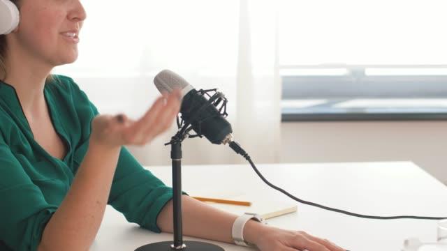 vidéos et rushes de femme avec le podcast d'enregistrement de microphone au studio - podcasting