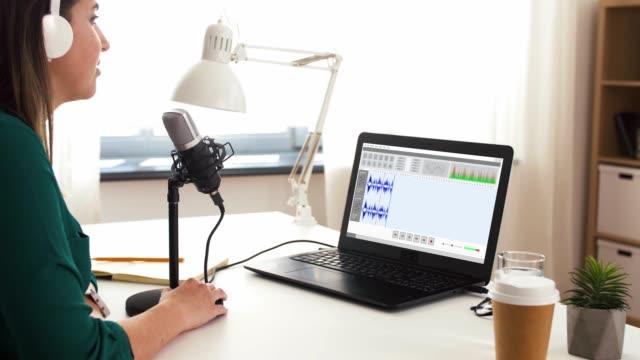 スタジオでマイク録音ポッドキャストを持つ女性 - 編集者点の映像素材/bロール